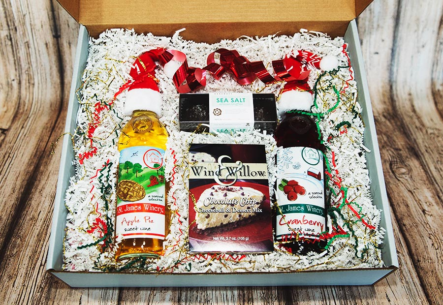 Holiday Gift Box including Santa hat wine bottle toppers, dark chocolate sea salt caramels, Wind and Willow Chocolate Chip dip, Apple Pie and Cranberry Wine
